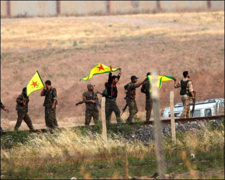 Kurdish YPG fighters hold their movement's flag near the Akcakale crossing gate between Turkey and Syrian Kurdistan on June 15, 2015 AFP