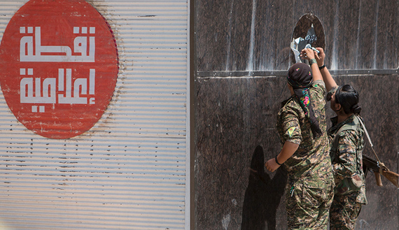 "Kurdish People's Protection Units (YPG) fighters remove an Islamic State sticker in Tel Abyad town, Raqqa governorate, June 16, 2015. With a string of victories over Islamic State, Syria's Kurds are proving themselves an ever more dependable ally in the U.S.-led fight against the jihadists and building influence that will make them a force in Middle Eastern politics. Aided by U.S.-led air strikes, the Kurdish-led YPG militia may have dealt Islamic State its worst defeat to date in Syria by seizing the town of Tel Abyad at the Turkish border, cutting a supply route to the jihadists' de facto capital of Raqqa city. The Arabic text on the left read: ""Media point"". REUTERS/Rodi Said - RTX1GSTO"