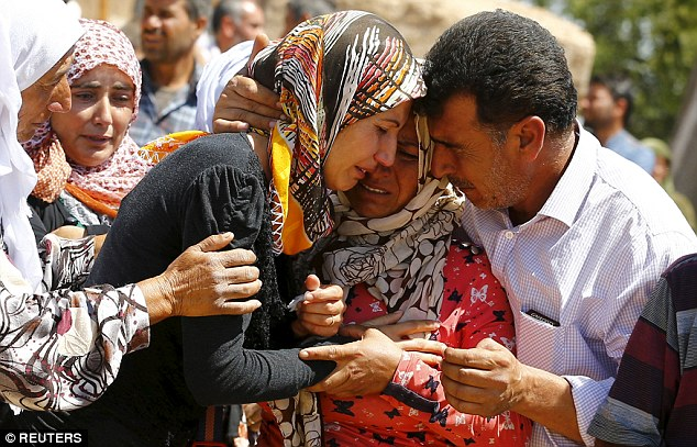 A family, in the border town of Suruc, Turkey, mourns the loss of their relative killed in Kobane - Reuters Read more: http://www.dailymail.co.uk/news/article-3139923/Kobane-doctor-describes-moment-maniac-ISIS-fighters-stormed-town-killing-women-children.html#ixzz3fNt6GX4i Follow us: @MailOnline on Twitter | DailyMail on Facebook