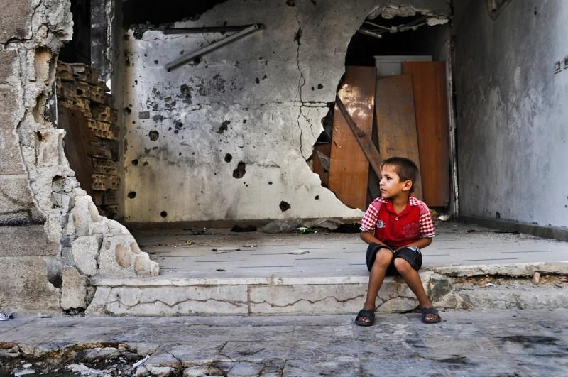Een Syrische jongen zit voor zijn vernielde huis (WFP/Abeer Etefa)
