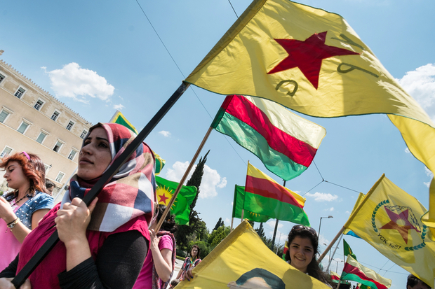 Kurdish women hold flags of YPG (People's Protection Units) and Rojava as they demonstrate in front of the Greek parliament in Athens on July 16, 2015. The United States does not support the establishment of an autonomous Kurdish entity in northern Syria, the US special envoy for the coalition against Islamic State extremists said on July 14.  AFP PHOTO / ANDREAS SOLARO / AFP / ANDREAS SOLARO