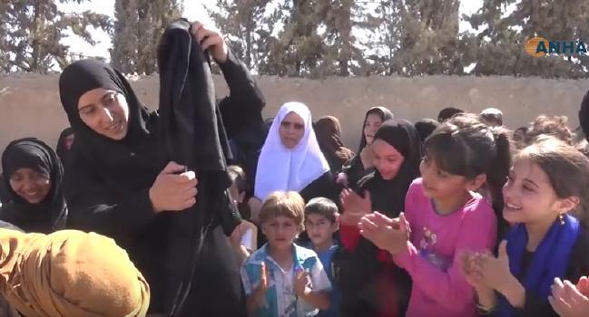 Een vrouw verbrandt haar burka na de bevrijding van Manbij (Menbic) door de Syrische Democartische Krachten. Foto: ANHA