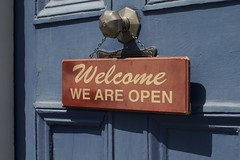 Welcome we are open bordje aan deur